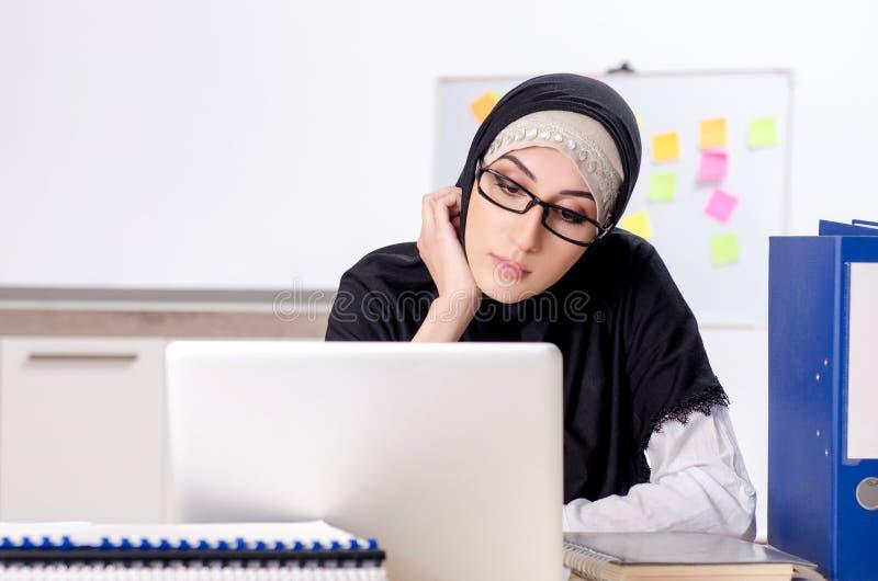 O empregado do sexo feminino no hijab que trabalha no escrit?rio fotos de stock