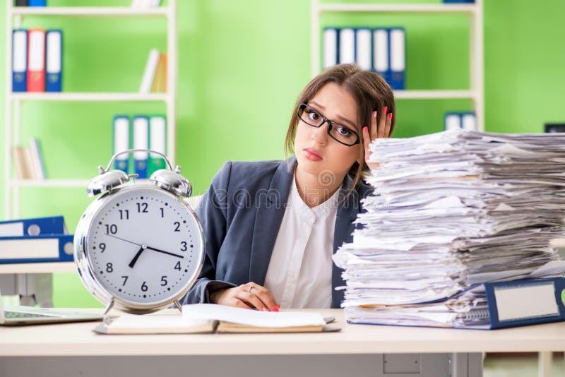 O empregado do sexo feminino novo muito ocupado com conceito em curso da gestão do documento a tempo foto de stock