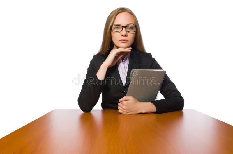 O empregado do sexo feminino que senta-se na tabela longa isolada no branco imagens de stock
