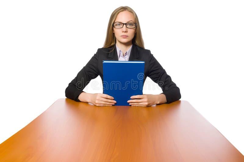 O empregado do sexo feminino que senta-se na tabela longa isolada no branco fotos de stock