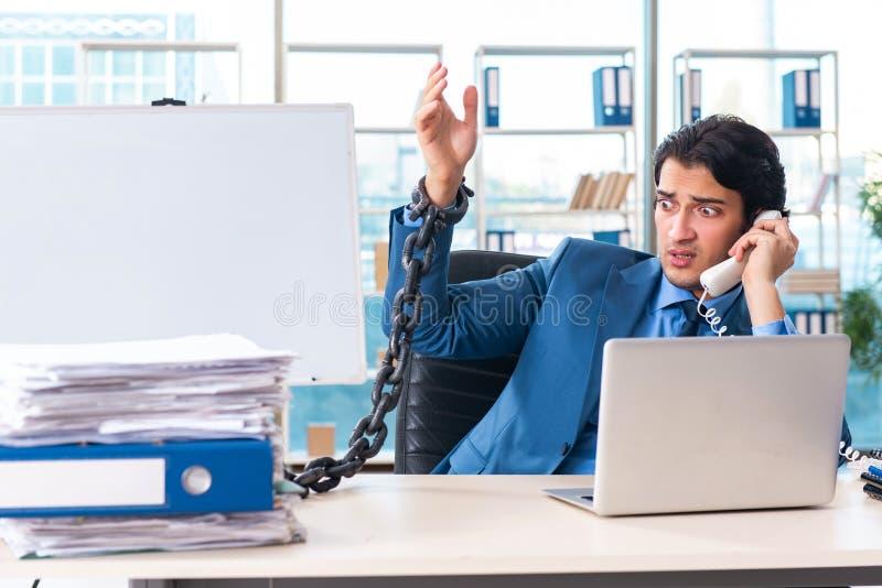 O empregado do sexo masculino acorrentado infeliz com trabalho excessivo imagens de stock