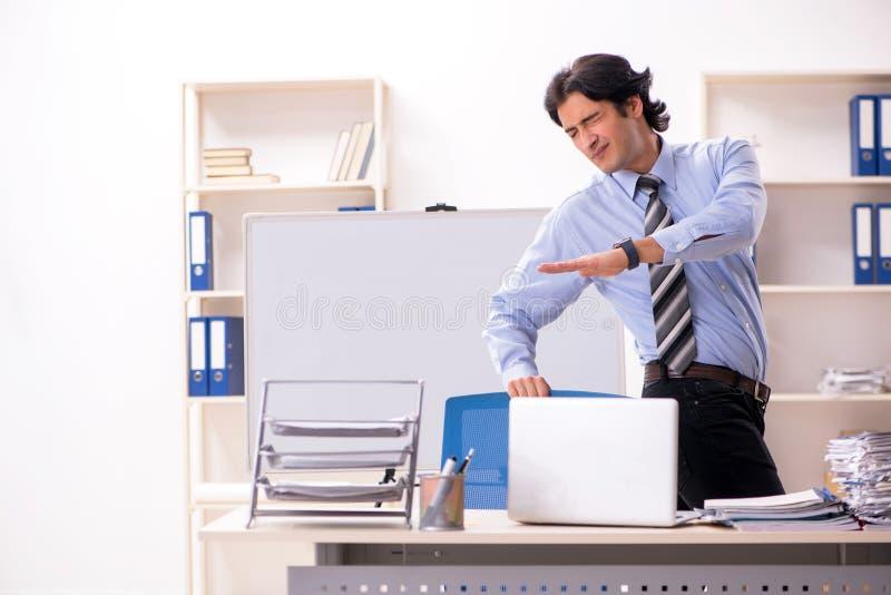 O empregado do sexo masculino considerável novo que faz exercícios no escritório foto de stock