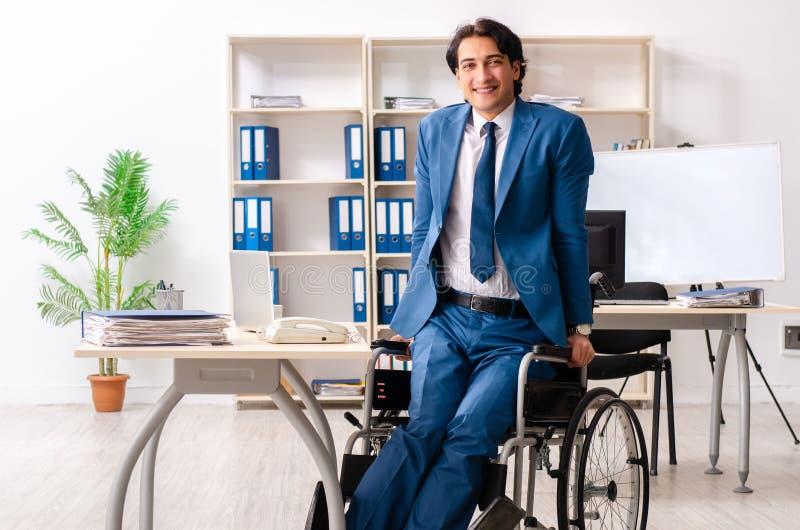 O empregado do sexo masculino no funcionamento da cadeira de rodas no escrit?rio fotos de stock