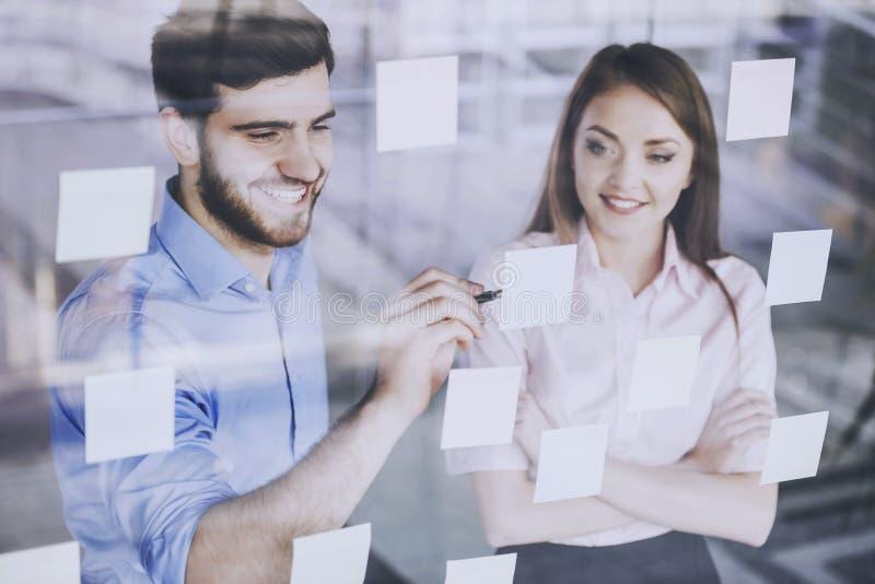 O empregado do sexo masculino novo escreve em etiquetas imagens de stock