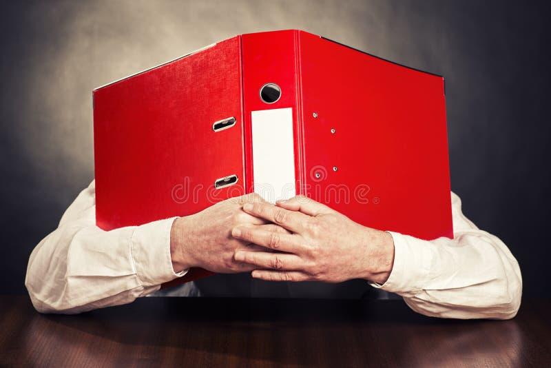 O empregado esconde a cara atrás da pasta de arquivos fotografia de stock