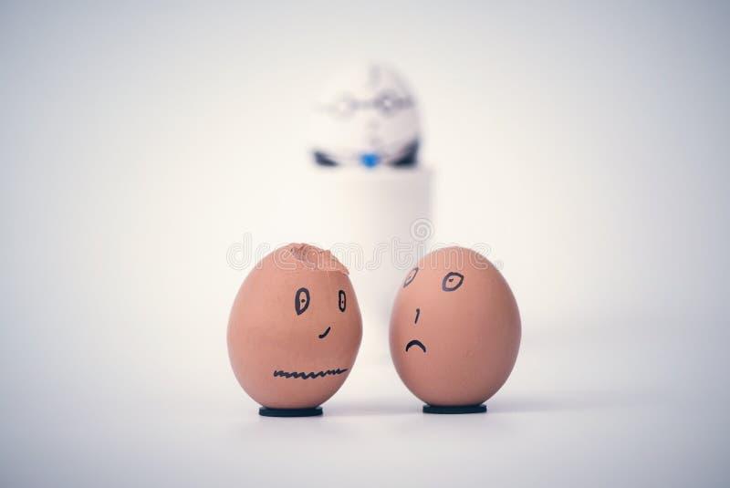 O empregado escuro quebrado de dois ovos sob a forma da cabeça humana queixa-se entre si Ovo do chefe no fundo fotos de stock royalty free