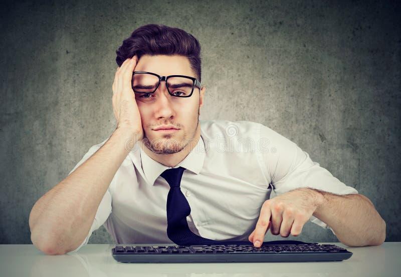 O empregado furado do homem que senta-se na mesa não tem nenhuma motivação a trabalhar imagem de stock