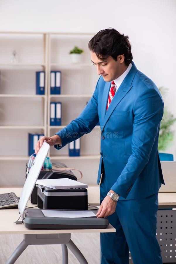 O empregado novo que faz cópias na máquina de copi foto de stock