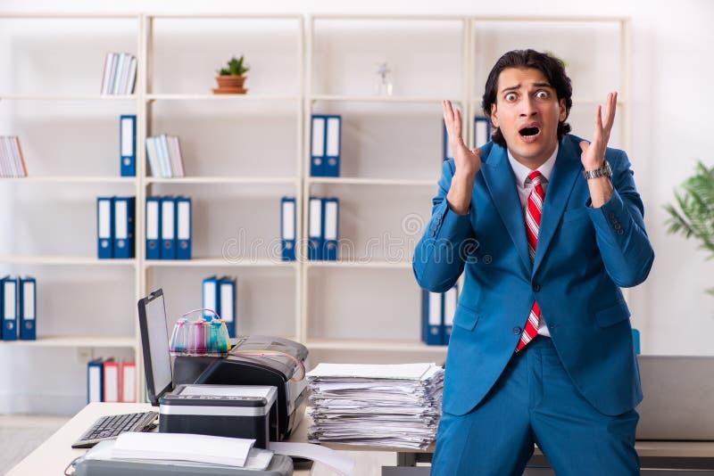O empregado novo que faz c?pias na m?quina de copi fotografia de stock royalty free