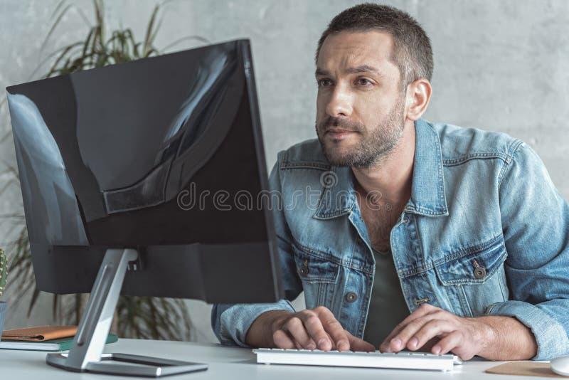 O empregado profissional está trabalhando no computador foto de stock