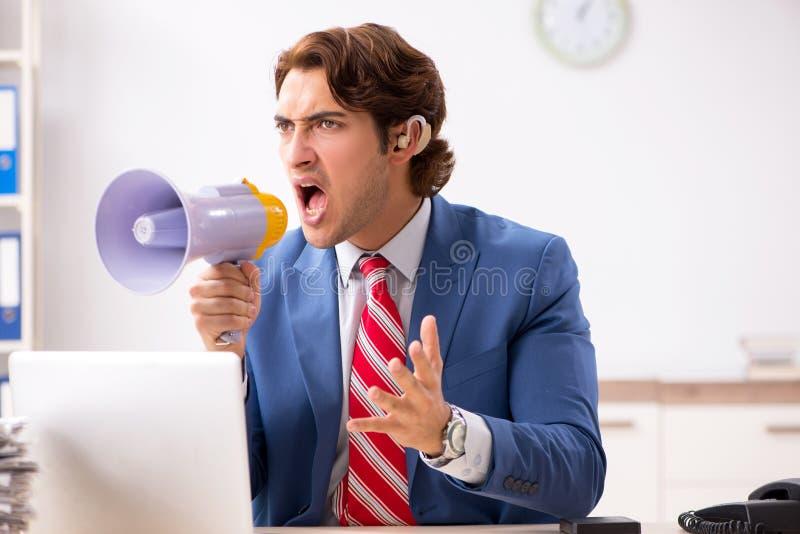 O empregado surdo que usa a prótese auditiva no escritório foto de stock