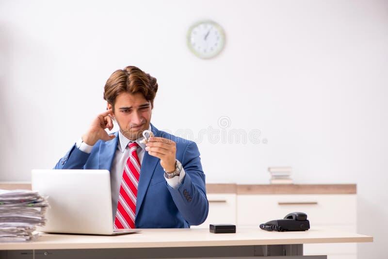 O empregado surdo que usa a prótese auditiva no escritório imagem de stock