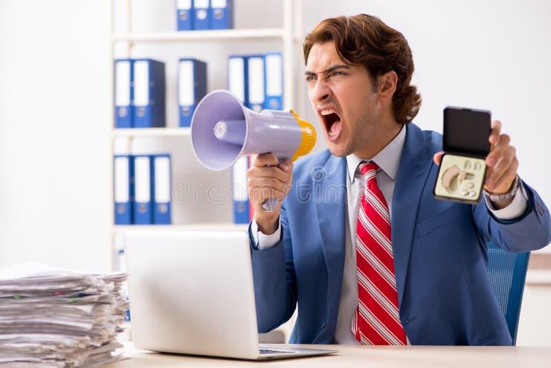 O empregado surdo que usa a pr?tese auditiva no escrit?rio foto de stock royalty free