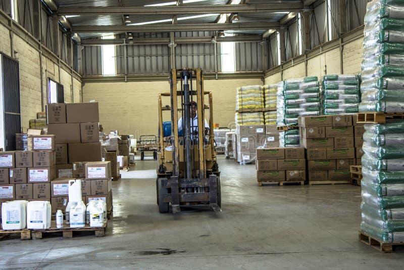 O empregado trabalha com uma empilhadeira para carregar um caminhão com as entradas agrícolas em Matao imagem de stock royalty free