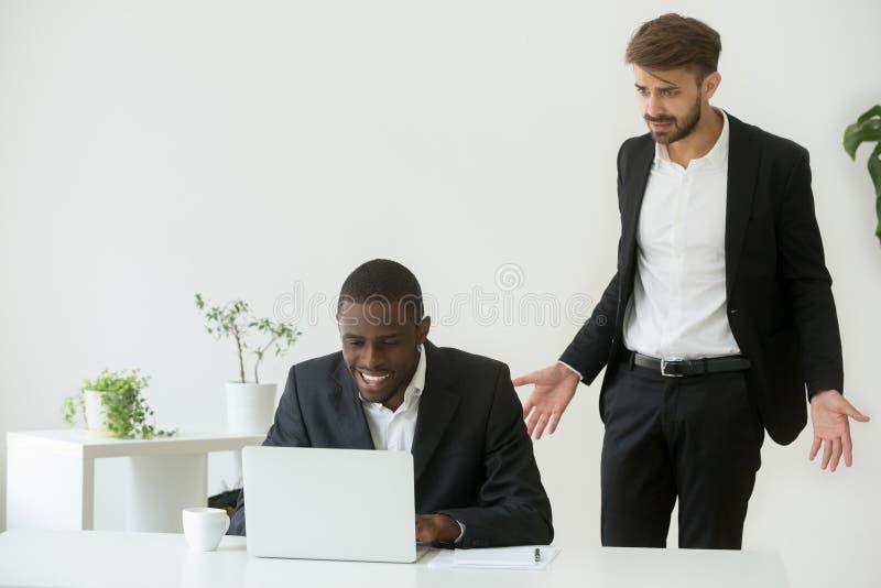 O empregador caucasiano chocou a observação do trabalhador preto manter distraído o du fotografia de stock