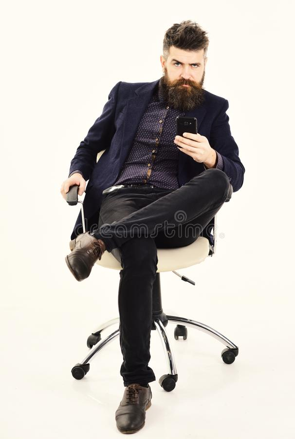 O empregador guarda o smartphone Diretor com barba longa e a cara séria O CEO senta-se na cadeira do escritório e olha-se ocupado fotos de stock