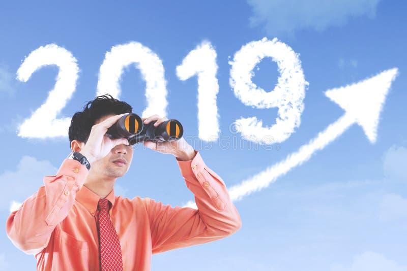 O empresário masculino olha o número 2019 imagens de stock
