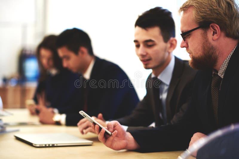 O empresário próspero do homem conecta ao Internet através do telefone celular ao se sentar na sala de conferências, fotografia de stock
