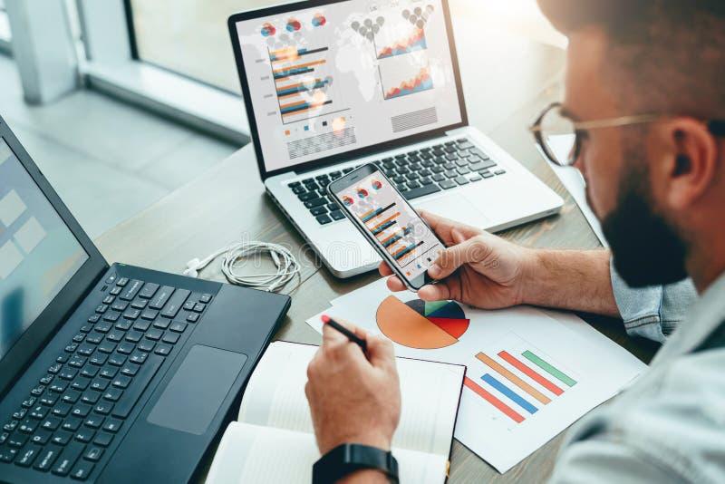 O empresário senta-se no escritório, usa o smartphone, trabalhando no portátil com cartas, diagramas na tela, faz anotações no ca fotografia de stock royalty free