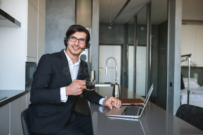 O empresário trabalha em casa remotamente com um laptop devido à quarentena do coronavírus fotografia de stock royalty free