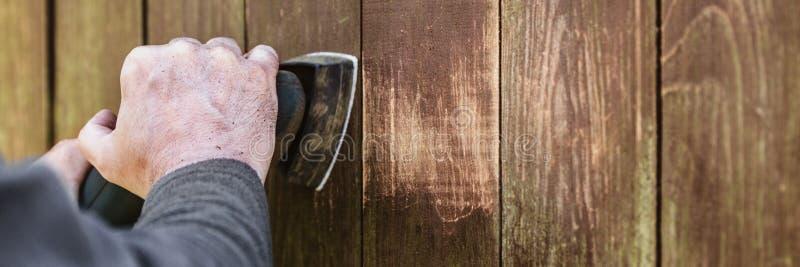O encabeçamento, carpinteiro está lixando placas de madeira resistidas com um elét. imagens de stock