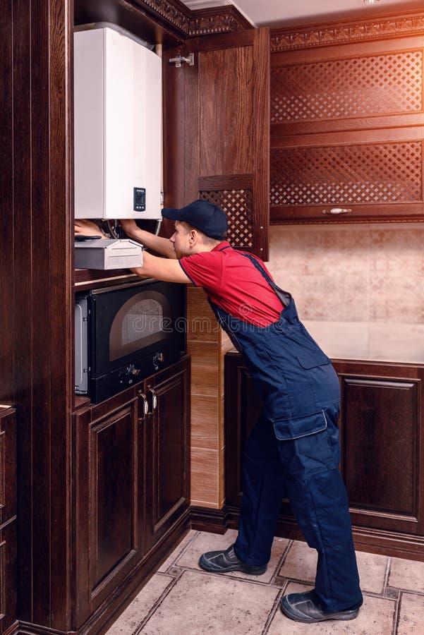 O encanador ajusta a caldeira de g?s antes de operar, profissional de seu of?cio imagens de stock