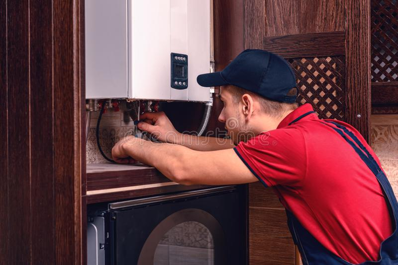 O encanador ajusta a caldeira de g?s antes de operar, profissional de seu of?cio imagens de stock royalty free