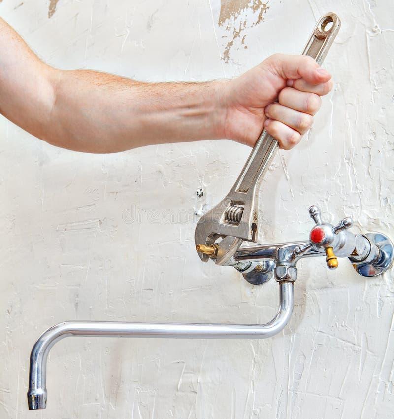O encanador entrega o torneira da válvula da torneira de água da fixação usando o sp ajustável imagens de stock