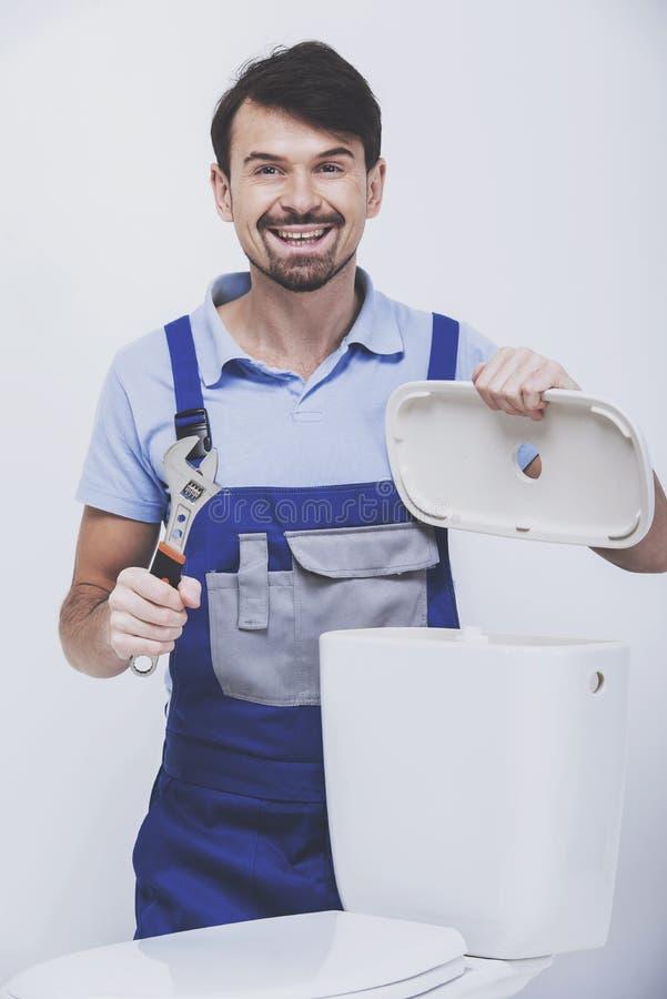 O encanador está reparando o toalete foto de stock