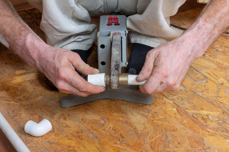O encanador masculino solda as tubulações plásticas do polipropileno com um instrumento elétrico para as tubulações de solda fotografia de stock