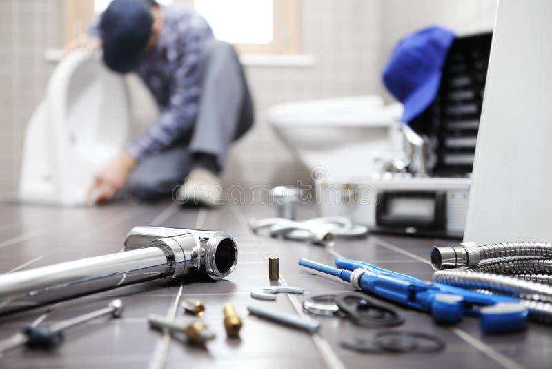 O encanador no trabalho em um banheiro, sondando o serviço de reparações, monta