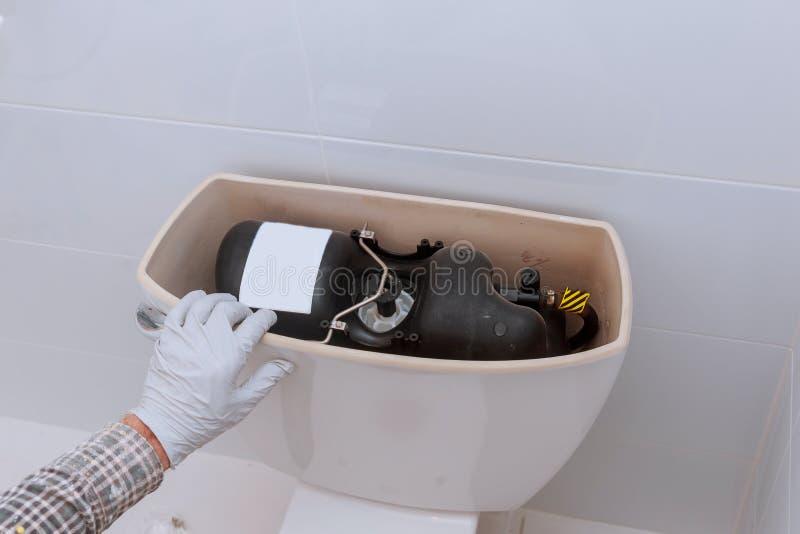 O encanador que repara o tanque do toalete no banheiro que sonda em casa muda o toalete fotografia de stock