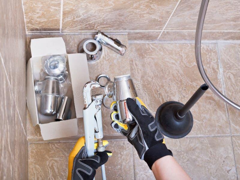 O encanador repara a armadilha do dissipador no banheiro fotografia de stock