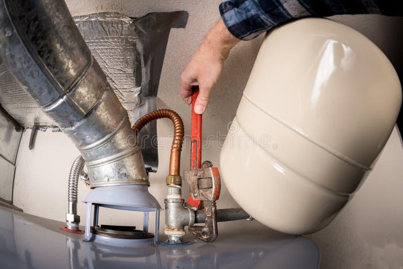 O encanador usa uma chave de tubulação em um aquecedor de água quente para apertar uma porca do metal fotografia de stock royalty free