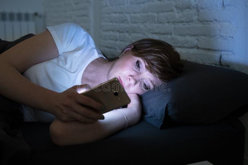 O encontro bonito novo da mulher furou na cama usando o telefone celular tarde na noite em um quarto escuro imagens de stock royalty free