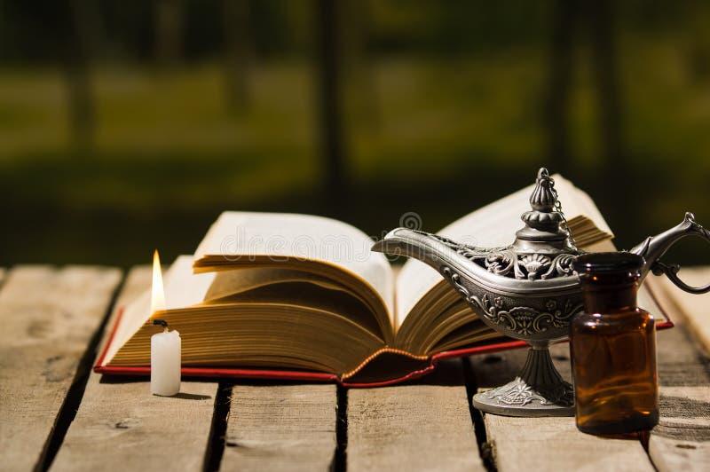 O encontro grosso do livro aberto na superfície de madeira, a lâmpada de Aladin e a cera candle o assento ao lado dele, ajuste bo imagem de stock