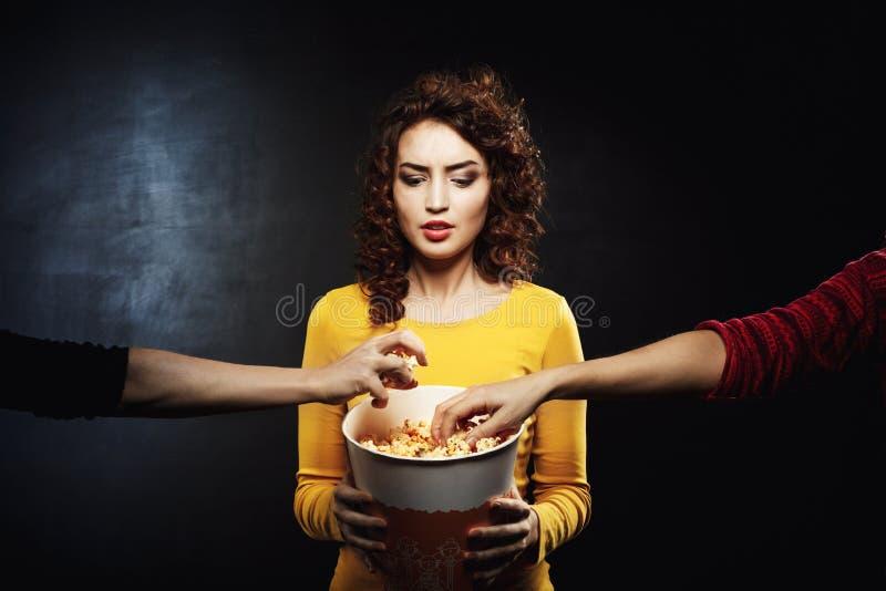 O ` engraçado t do doesn da mulher gosta de compartilhar de petiscos com os amigos no cinema fotografia de stock