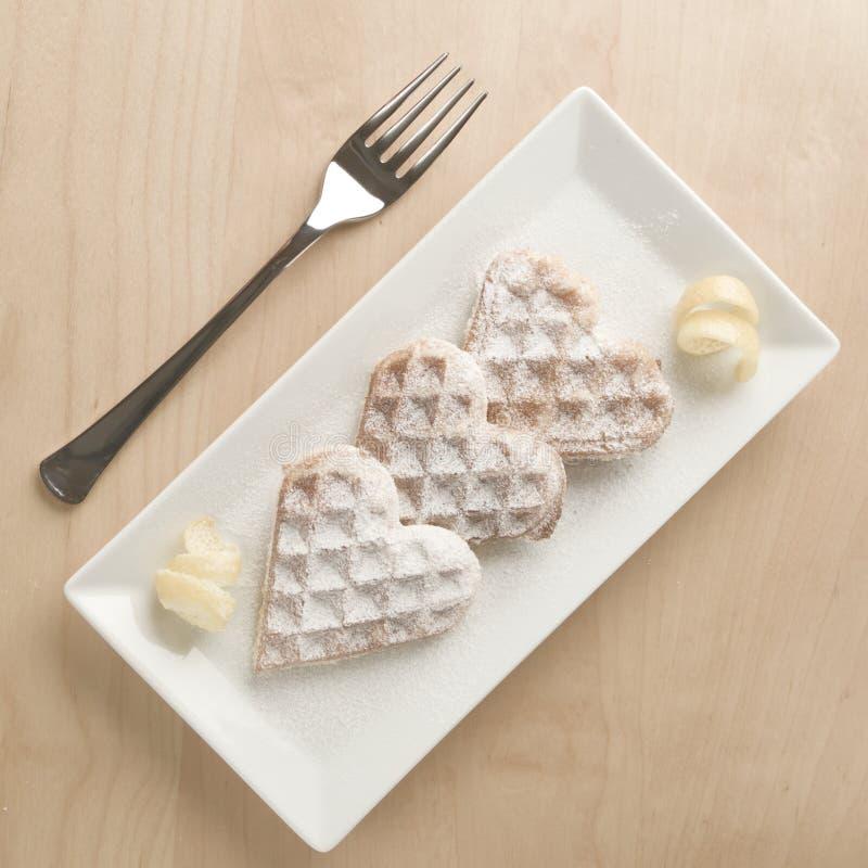 O entusiasmo de limão dos waffles do coração, açúcar pulverizado serviu em p retangular fotografia de stock royalty free