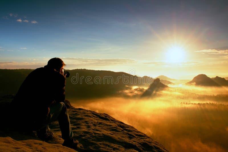 O entusiasta feliz da foto está apreciando o milagre fantástico da natureza no penhasco na rocha Fole sonhador da paisagem do fog fotografia de stock