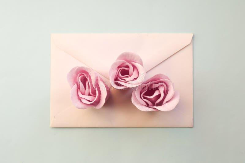 o envelope branco, rosa três aumentou flores em um fundo azul Configuração mínima do plano foto de stock