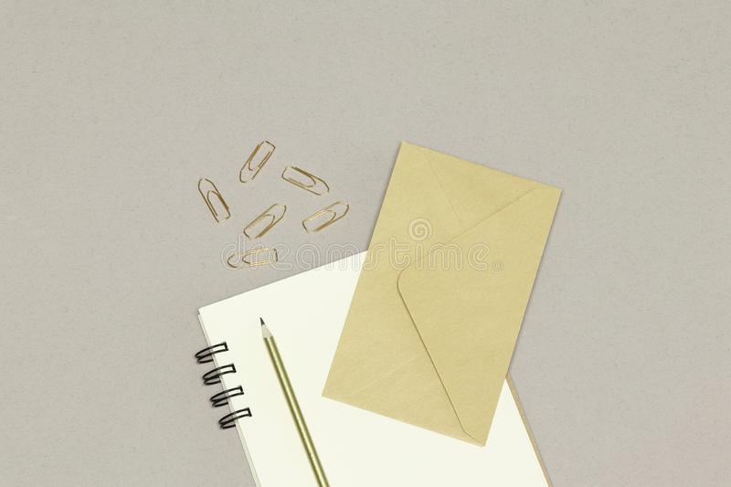 O envelope de kraft, as notas, o lápis dourado & os clipes de papel, no fundo branco fotos de stock royalty free
