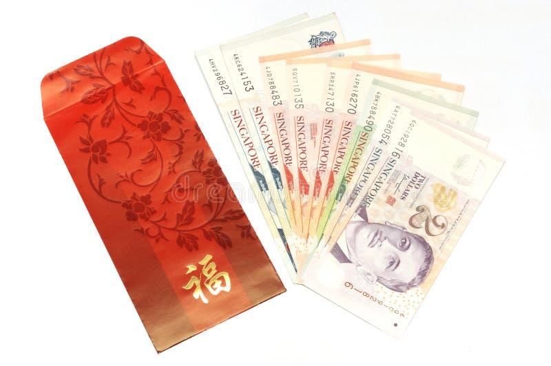 O envelope vermelho com dinheiro de Singapura nota de lado a lado fotos de stock