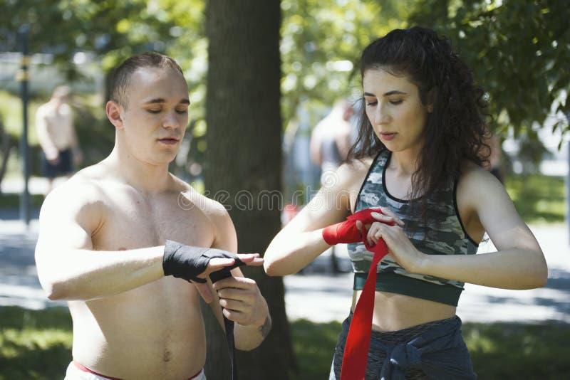 O envoltório masculino do pugilista sua jovem mulher das mãos ajuda-o, exercício no parque fotografia de stock royalty free