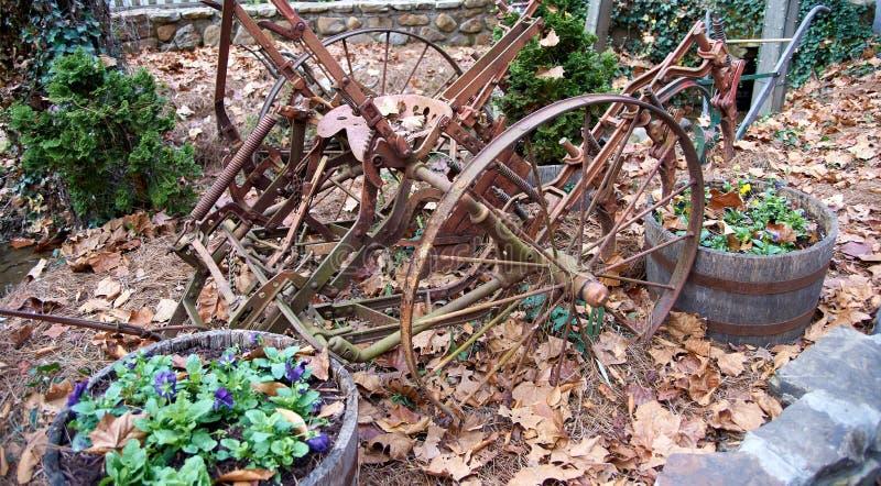 O equipamento agrícola velho rústico que senta-se na queda sae foto de stock