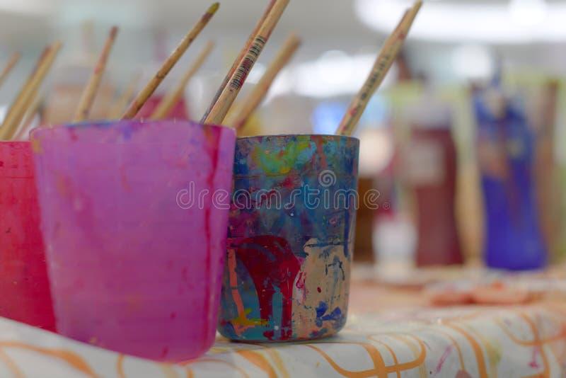 O equipamento colorido da aquarela tal como o vidro dos paintbrushs e a bandeja da cor estão disponíveis para crianças imagem de stock