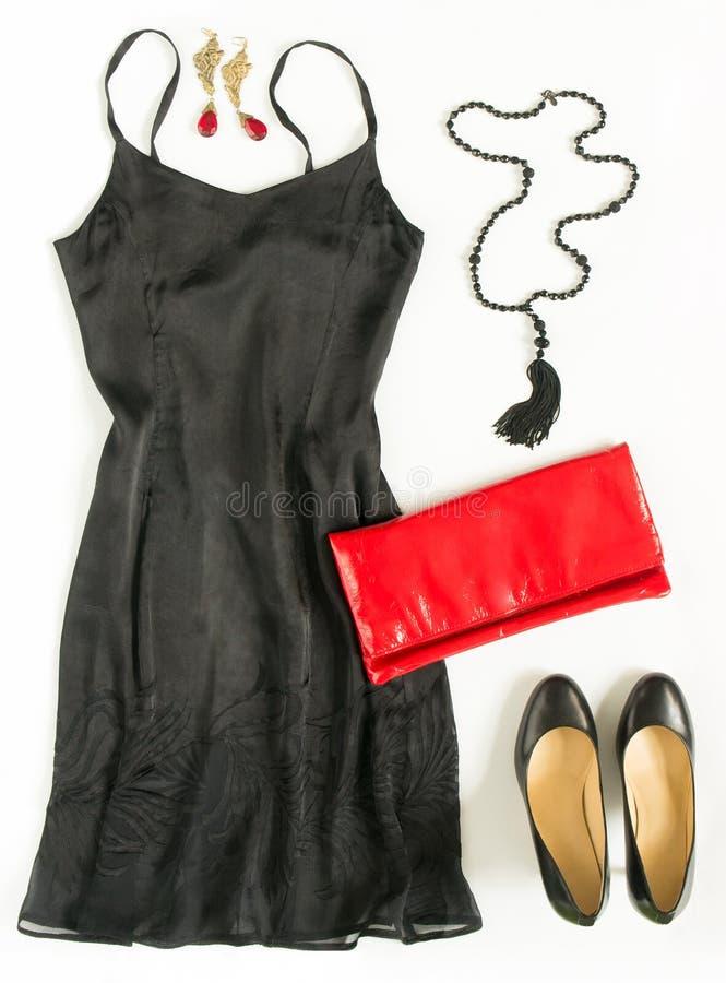 O equipamento do vestido de cocktail, noite para fora olha no fundo branco Pouco vestido preto, embreagem vermelha da noite, sapa imagens de stock