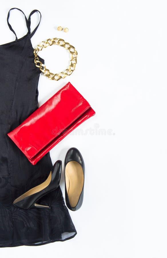 O equipamento do vestido de cocktail, noite para fora olha no fundo branco Pouco vestido preto, embreagem vermelha, sapatas preta fotos de stock