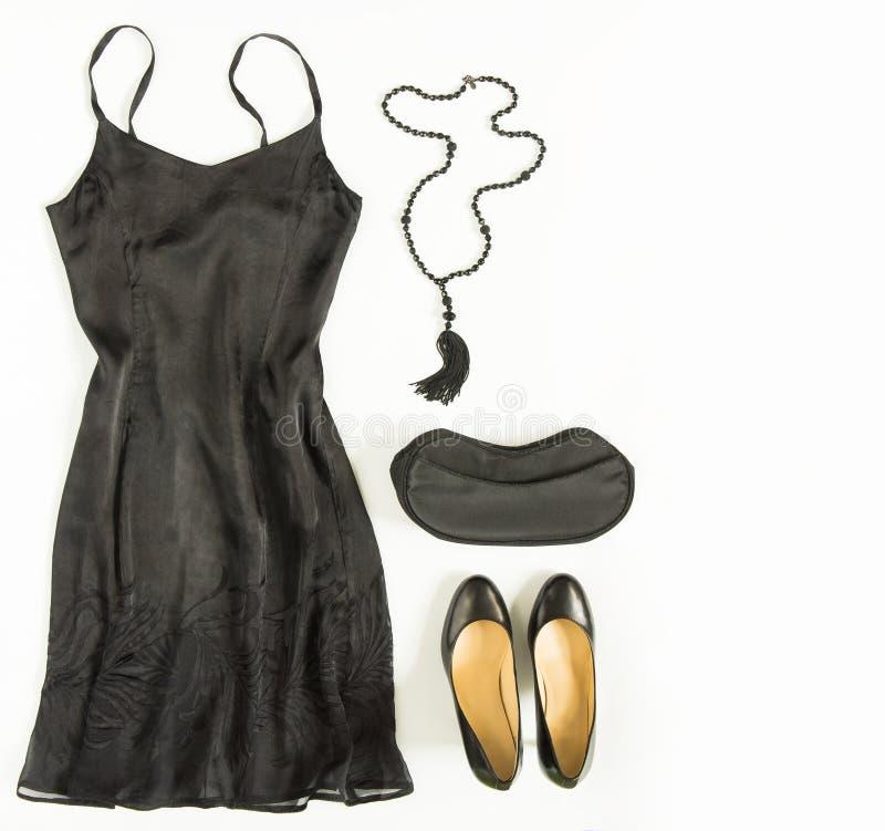 O equipamento do vestido de cocktail, noite para fora olha no fundo branco Pouco vestido preto, saco de noite, sapatas pretas, co foto de stock
