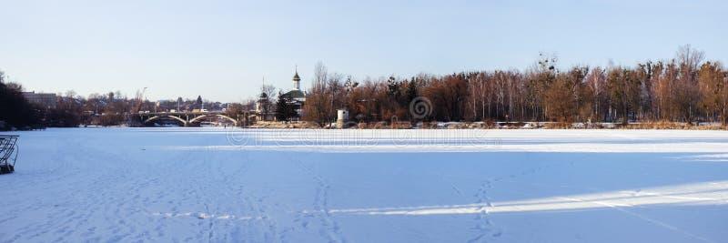 O erro do sul do rio congelado e nevado e e na distância uma ponte e um templo Blessed Xenia de Peterburg foto de stock