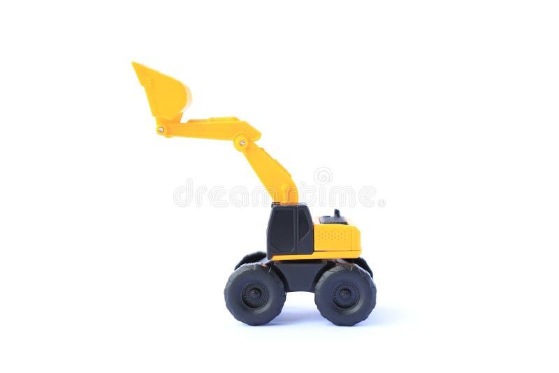 O escavador amarelo do carro de brinquedo isolado em fundo branco Modelo de brinquedo de retroenxada para crianças imagem de stock